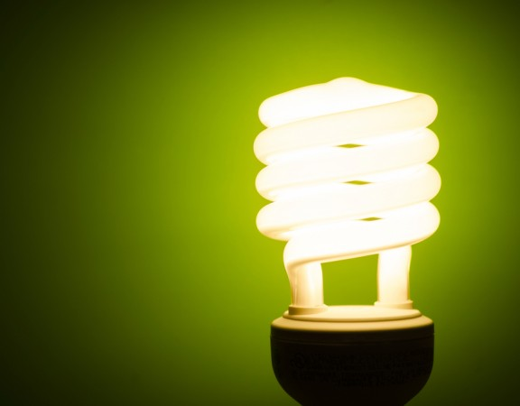 Energy efficient light bulb lit up in front of a green background